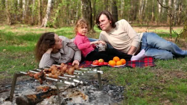 Familie liegt auf kariertem Gras, Teller mit Früchten liegen daneben