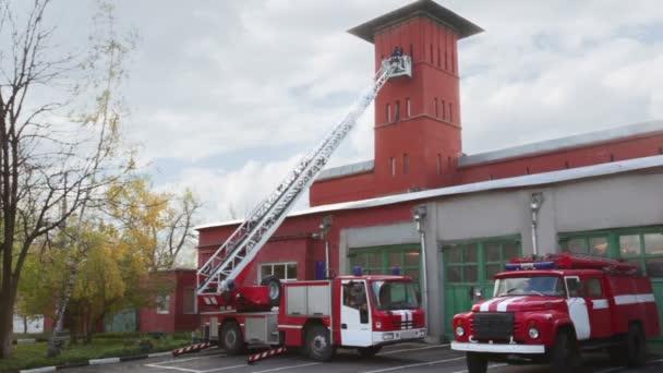 požární stanice, dvě červené hasičské auto s dlouhý žebřík