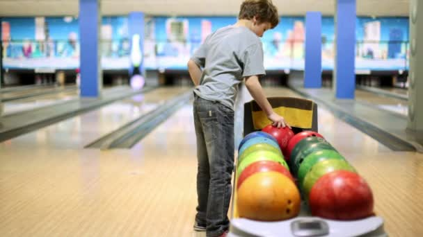 malý chlapec bere bowlingovou kouli a hází to porazit kuželky