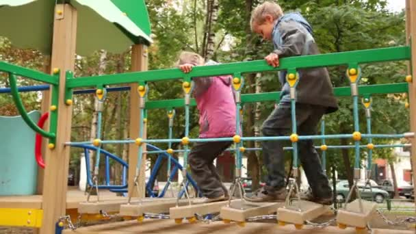 Little girl and boy jump hang down steps on playground