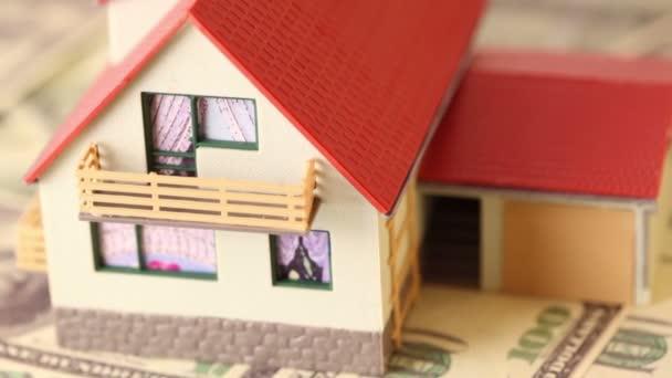 dům hraček s červenou taškovou střechou na dolarů bankovek