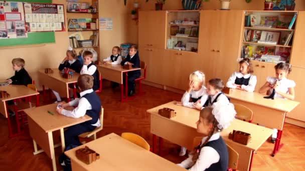 Iskolások ül az osztályban, egy fiú Térkép digitális játék az osztálytársai