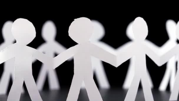 viele Papiermenschen stehen im Kreis und halten sich an Händen, drehen sich