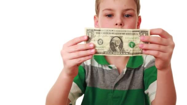 Boy carefully studies bill denominations of one dollar