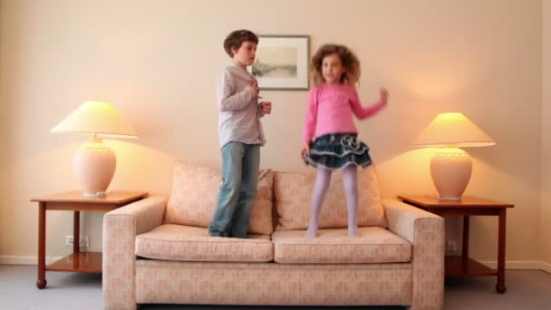 Two kids jump on sofa and then run away from room with lamps on each side