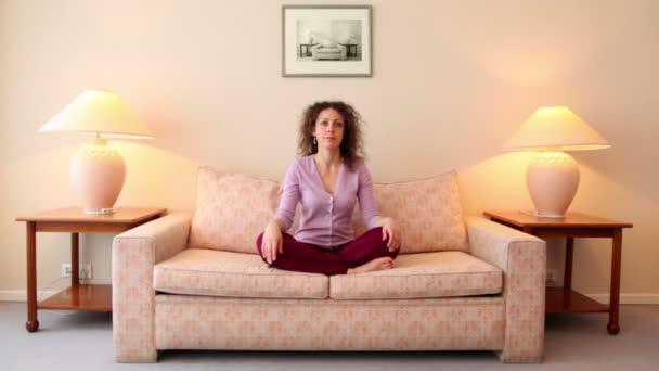 žena sedí na pohovce v představovat lotos, pak zavře oči a medituje