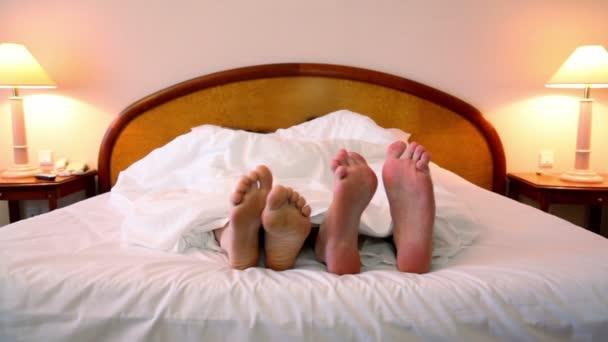 muž s žena ležela v posteli pod deku a kroky bosých nohou