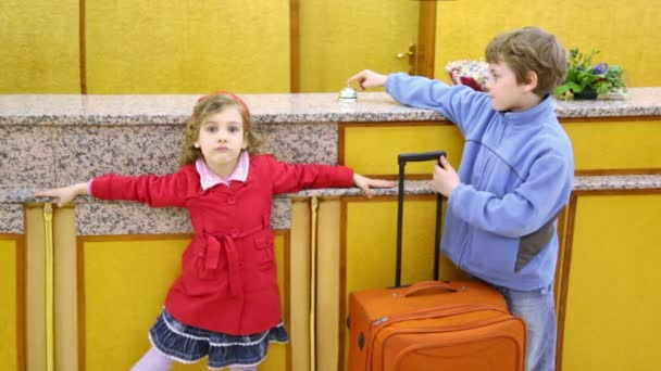 Two kids boy with girl stand with trunk at hotel reception and ring service bell
