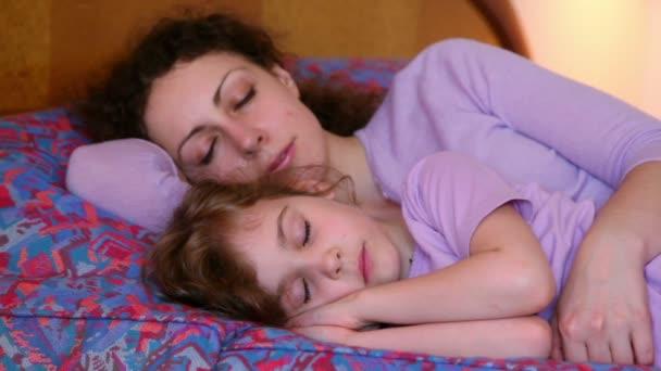 Kislány alszik kezét feje, anyja közelében