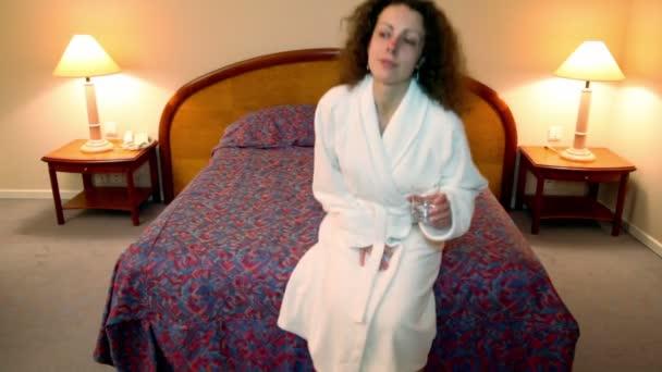 donna arriva alla camera da letto, si siede sul letto e beve lacqua dal vetro