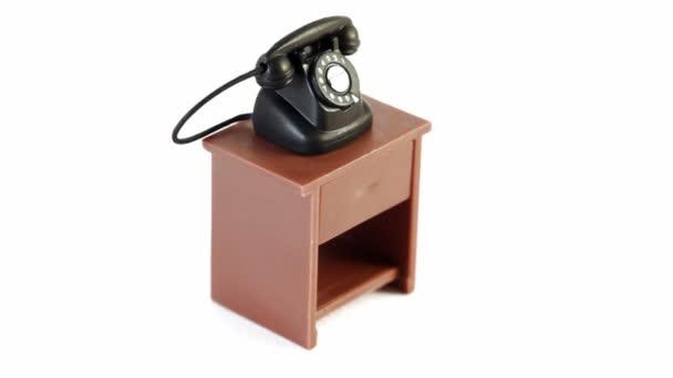 schwarzes Spielzeugtelefon auf kleinem Tisch