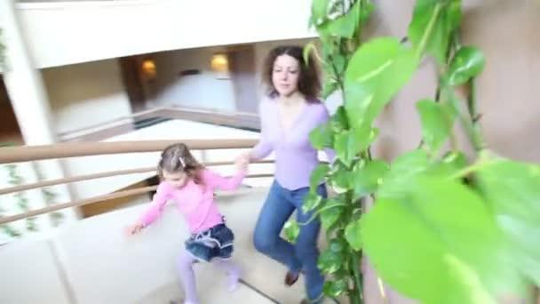 matku a její děti chodit nahoře točité schodiště s rostlinami na zdi ve více podlažích
