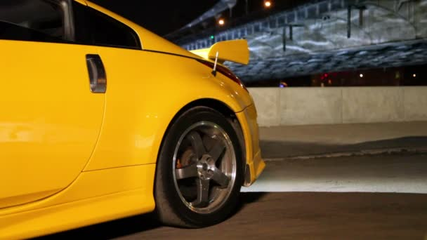 Gelber Sportwagen steht nachts im Hintergrund der Brücke