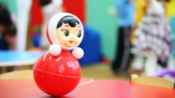Roly-Poly hračky se netočí na stole, v rozostření pozadí děti hrají