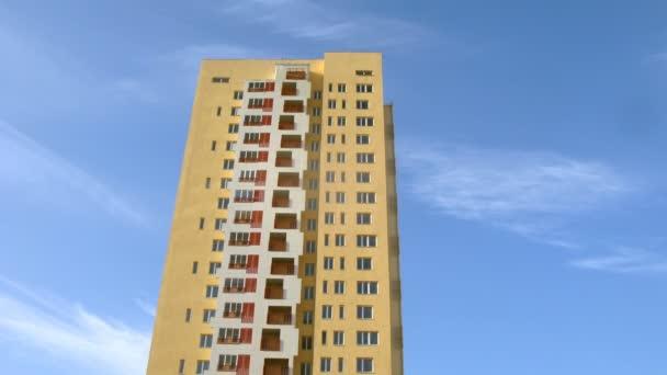 Hochhaus in gelber Farbe steht vor blauem Himmel