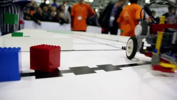 mnoho lidí dívat na robota se pohybuje a vzít kostka