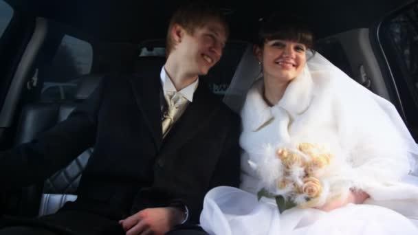Novomanželé sedí v autě společně