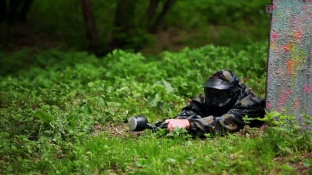 chlapec paintball hráč leží s pistolí v záloze na trávníku hned vedle plotu