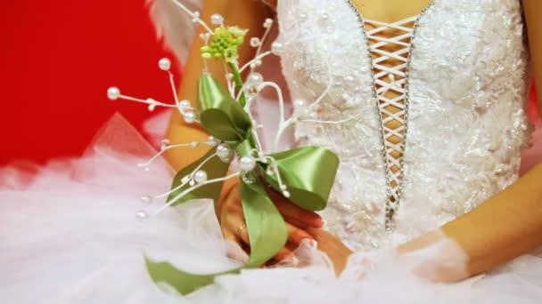 ruce nevěsta ve svatebních šatech drží kytici zdobené perlami