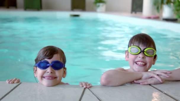 Zwei Kinder in Schwimmbrille bleiben am Beckenrand