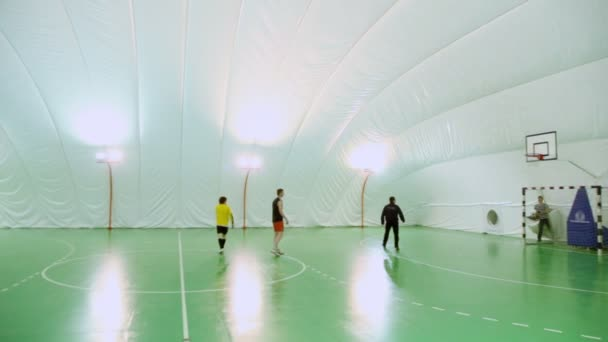 Four students play soccer on football field