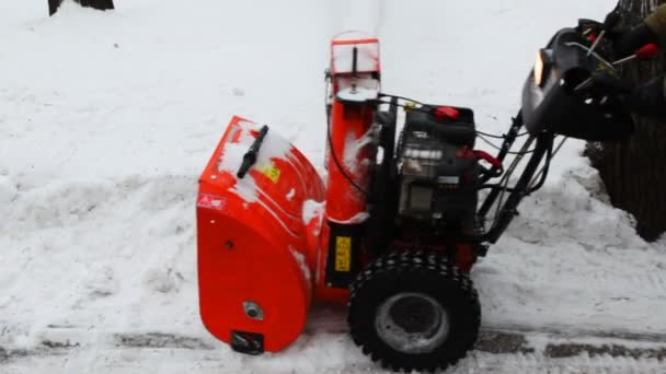 Man cleans snow with small manual machines