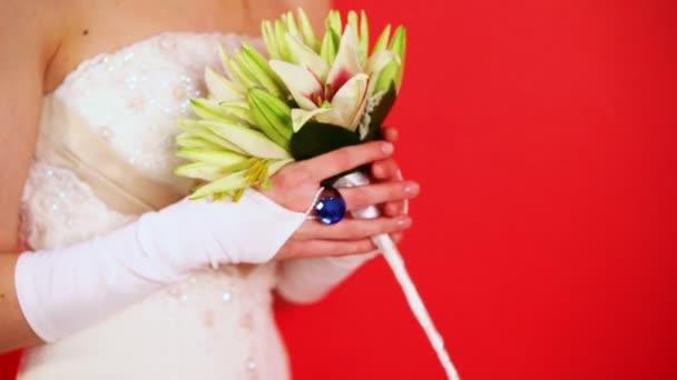 nevěsta v bílých šatech drží kytici lilií