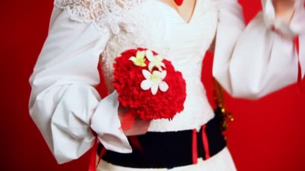 nevěsta ve svatební šaty v lidovém stylu držení kytice karafiátů
