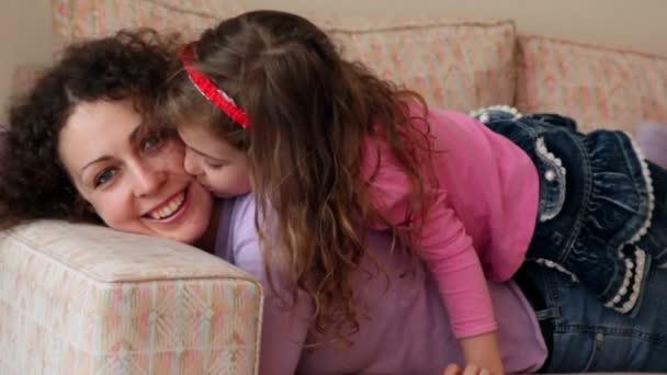 holčička leží na matce nohy a polibky její tváře, detailní pohled na pohovce