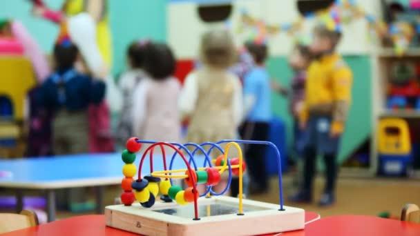 hlavolam hračka stojící na stole, v rozostření pozadí děti hrají