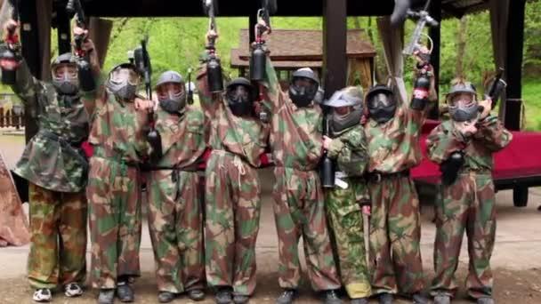osm teenagerů paintball tým postavit a cíl zbraň pro fotoaparát před letní dům