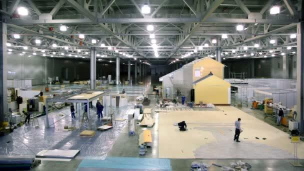 Labourers work on building site in exhibition hangar