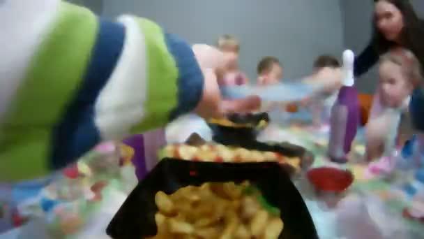 Gyermekek ünnepli születésnapját ünnepi asztal körül
