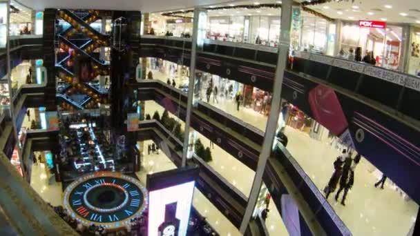 uprostřed haly kde chodí lidi je velké hodiny v nákupním centru