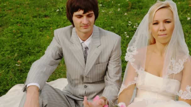 Man and woman in wedding dresses sit on meadow fastened by handcuffs to each other