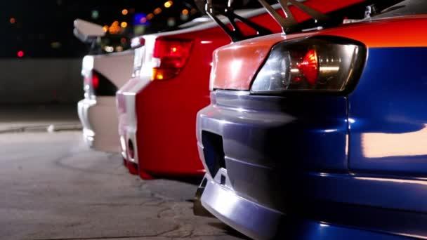 tři auta s barevnými sport design v noci