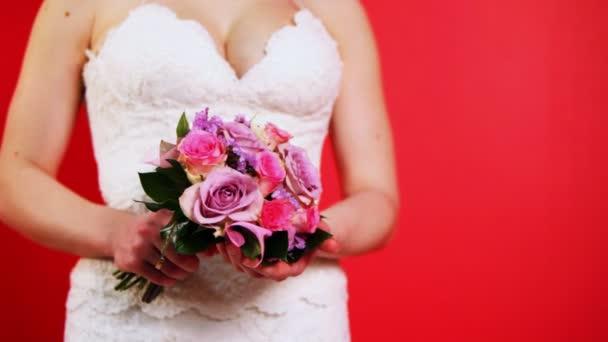 nevěsta v bílých šatech drží kytici růží