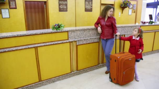Mother and her daughter stand with trunk at hotel reception