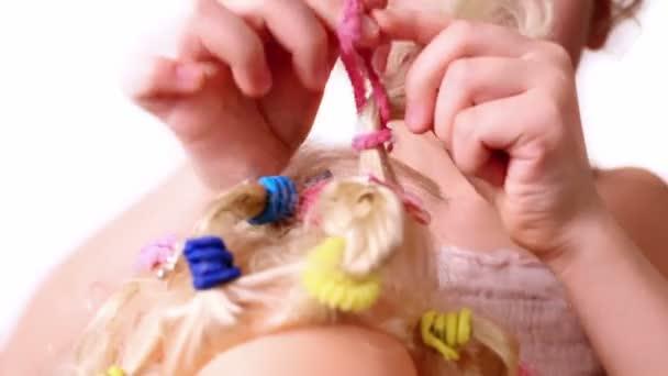 holčička používat gumičkou k splétat vlasy panenky