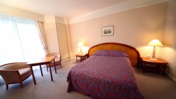 ložnice s lampami na každé straně postele a dvojice křesla u stolu