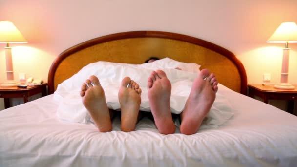 muž a žena spát v posteli pod dekou v místnosti s lampami na každé straně