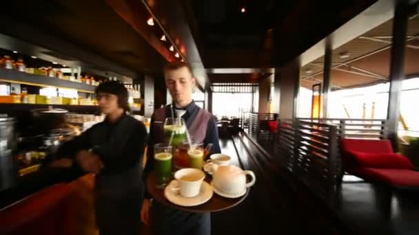 Waiter carries tray with drinks in restaurant lounge
