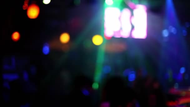 People in night club with colorful illumination and video screen
