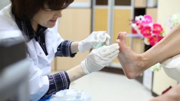 kosmetička pedikúra ženě a tře kosmetické oleje v jeho noha