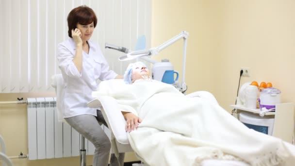 paziente si trova in poltrona di cosmetologia ed estetista parla per telefono