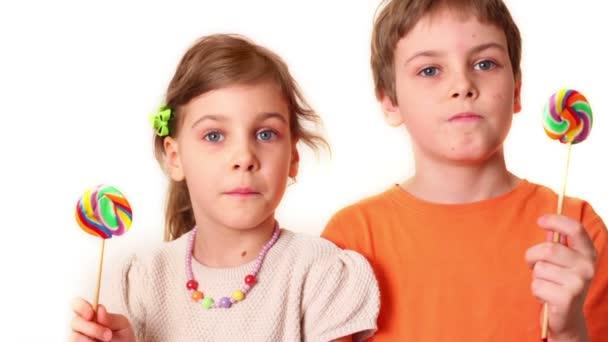 dvě děti chlapec a dívka drží lízátka a pak se podívejte na sebe