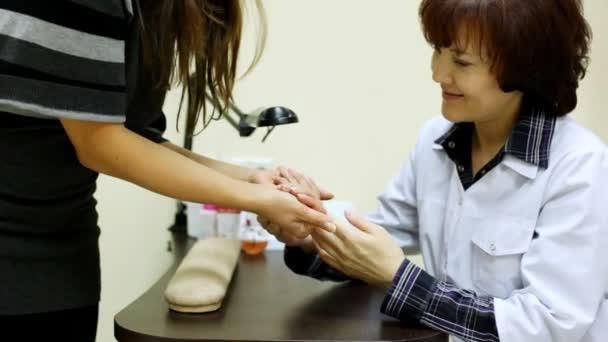 Kosmetikerin berät Kunden und Händen im Salon zu prüfen