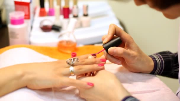 Cosmetician accurately covers nails of client with pink nail polish
