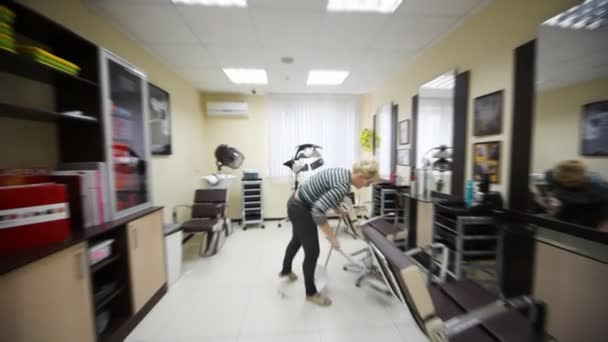 Woman-hairdresser does cleaning in hairdressing salon
