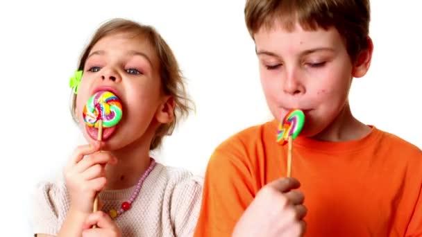 dvě děti chlapec a dívka jíst lízátka